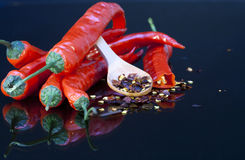Red chili peppers and spoonful of  seed Royalty Free Stock Photos