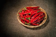 Red chili peppers on the wicker dish Stock Photos