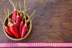 Red Chili peppers in a wooden bowl. Red Chili pepper pods in a wooden bowl on a rustic wooden table with fabric ribbon with copy space as menu card Royalty Free Stock Photography