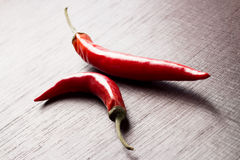 Red chili peppers on wooden table Royalty Free Stock Photos