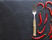 Red chili peppers on a wooden table with a fork, concept, top view Royalty Free Stock Image