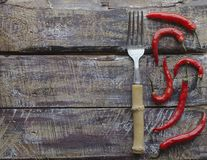 Red chili peppers on a wooden table with a fork, concept, top view Stock Images