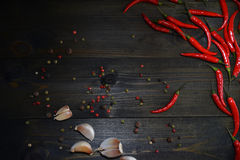 Red chili peppers on the wooden texture desk with garlic and different sorts of pepper. Appetizer concept Stock Image