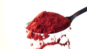 Red chili powder falling from the iron spoon. White background. Slow motion