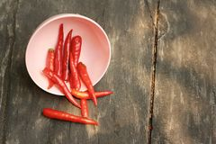 Red chilies in a pink bowl on wooden background Royalty Free Stock Photos