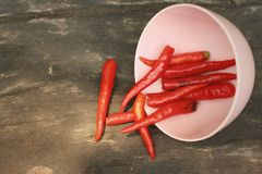 Red chilies in a pink bowl on wooden background Stock Image