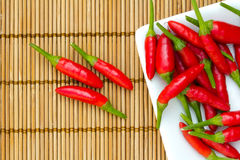 Red chilli. Es in a white plate on a bamboo mat Stock Photo