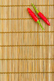 Red chilli on a bamboo mat. Two red chilli at the right corner of a bamboo mat, empty left space for text Royalty Free Stock Photo