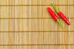Red chilli on a bamboo mat. Two red chilli at the right corner of a bamboo mat, empty left space for text Stock Photo