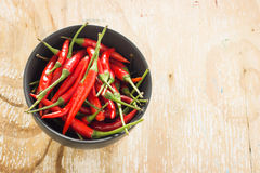 Red chilli in a black bowl. Red chilli in a black bowl on wooden table Stock Image