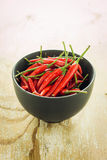 Red chilli in a black bowl. Red chilli in a black bowl on wooden table Royalty Free Stock Photo
