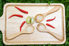 Red chilli, lime and wooden spoon full of rice. On the wooden tray placed on the green grass Stock Photo