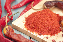 Red chilli pepper piece. And ground pepper on a wooden board Royalty Free Stock Photos
