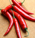 Red Chilli Peppers. On a wooden chopping board Royalty Free Stock Images