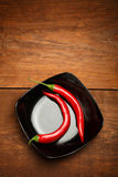 Red chilli peppers on black ceramic plate standing on brown wood. Two bright red ripe hot cayenne peppers on black ceramic plate standing on brown wooden table Stock Photography