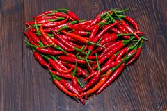 Red chilli peppers on wooden table placed in shape of heart. Red cayenne chilli peppers on dark wooden table placed in the shape of heart stock photo