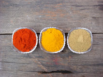 Red chilli, turmeric and coriander powder in bowl. Indian spices red chilli, turmeric and coriander powder in bowl on wooden board Stock Photography