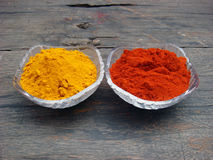 Red chilli and turmeric powder in bowl on the wooden. Red chilli and turmeric powder in crystal bowl on the wooden royalty free stock photography
