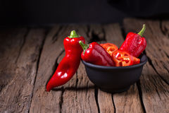 Red chilly pepper on wooden black background. Red hot chili pepp Stock Images