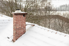 Red chimney and roof covered with snow Royalty Free Stock Photos