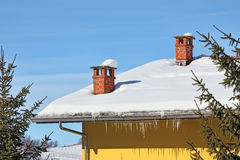 Red chimneys on snowy roof. Piedmont, Italy. Royalty Free Stock Photo
