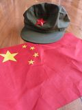 Red China: Chinese Flag with Red Guards Hat. Chinese red PRC flag and Red Guards Cultural Revolution hat arranged to symbolize Chinese communism and patriotism stock photo