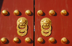 Red chinese door with a lion/dragon head Royalty Free Stock Photos