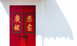 Red chinese gate in white cement with black shadow Stock Photos