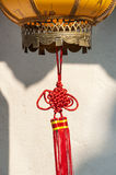 Red Chinese knot decoration attached to a traditional lantern royalty free stock image