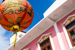 Red Chinese lantern. Against blue sky & pink facade of Sino-Portuguese townhouse in Phuket Old Town, Thailand Royalty Free Stock Photography