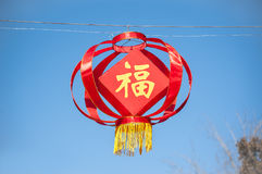 Red Chinese lantern bearing the Chinese character fu, meaning good fortune or happiness, hanging against a clear blue sky Royalty Free Stock Image