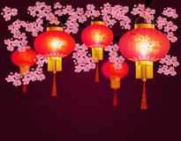 Red Chinese lanterns hanging in the park. Sakura. Round shape with patterns. Stock Photo