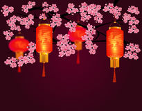 Red Chinese lanterns in a park. Cylindrical and round shape with a picture of the cock. Against the backdrop of pink Stock Images