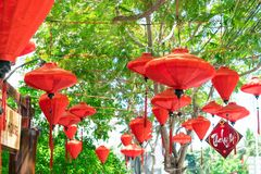 Red chinese lanterns on trees with green branch in sunlight royalty free stock photos