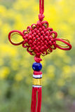 Red Chinese node  in yellow background. A single red Chinese node in the background of yellow flowers.Chinese node is stand for reunion,happiness,joy and rich Royalty Free Stock Photography