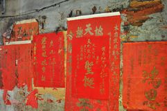 Red Chinese posters on a weathered wall in Bangkok, Thailand.  Stock Photos