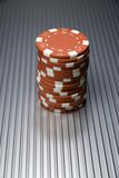 Red Chips. A stack of red casino or poker chips on a silver tin surface Royalty Free Stock Photo