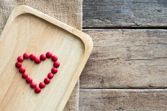 Red chocolate candies arrange in heart shape on wooden plate on gunny sack cloth on wood table. With copy space, top view Royalty Free Stock Images