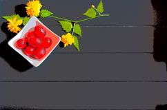 Red chocolate Easter eggs and yellow flowers with dark wooden background stock photos