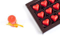Red chocolate hearts in box and candle Royalty Free Stock Images