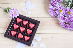 Red chocolate hearts in box and flowers on wooden table Stock Image