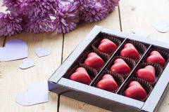 Red chocolate hearts in box and flowers on wooden table Stock Photo