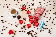 Red chocolate hearts in a glass jar and a cup of espresso coffee Royalty Free Stock Photography