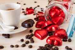 Red chocolate hearts in a glass jar and an espresso coffee. With coffee beans on a table Royalty Free Stock Photography