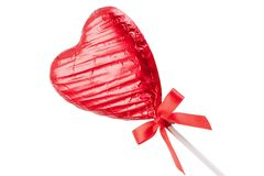Red Chocolate love heart lollypop angled. Red Chocolate love heart lollypop with a red ribbon bow on a stick. Isolated on a white background angled Stock Photo