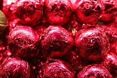 Red chocolate wrapped balls. A pile of chocolate truffles in shiny red wrappings Stock Images