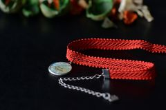 Red choker with a map pendant on a dark background. Close up stock image