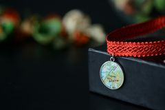 Red choker with a map pendant on a dark background Royalty Free Stock Image