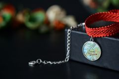 Red choker with a map pendant on a dark background Stock Photo