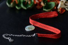 Red choker with a map pendant on a dark background Stock Photography